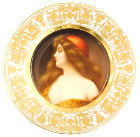 A 19thC Vienna porcelain cabinet plate, decorated with a portrait of a young lady with flowing brown hair and a red hat, titled Una Gitana, signed Wagner, within a pink and elaborate gilt border, 24.5cm diameter.