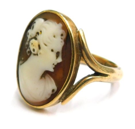 A late 19thC shell cameo ring, the oval cameo looking to the right, on shaped shoulders, yellow metal, stamped 9ct, ring size N, 5.1g all in.