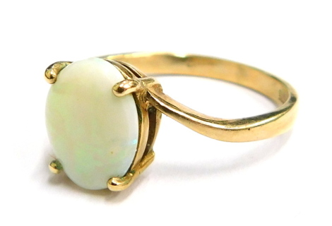 An opal set dress ring, in four claw setting with twist design shoulders, yellow metal, stamped 375, ring size M, 2.1g all in, boxed.