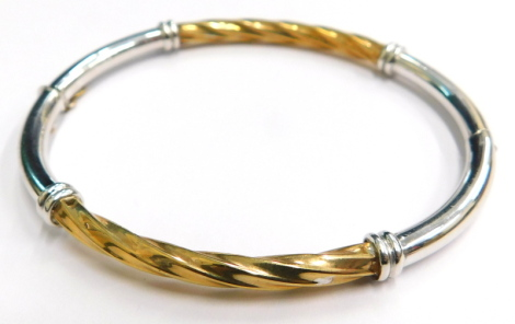 A 9ct gold hinged bangle, of two colour design, with silvered and yellow gold finish, the central panel of twist design, on hinge with safety clasp, maker's stamp H M Limited, 7cm diameter, 7g all in, boxed.