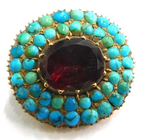 A Victorian brooch, the central oval panel set with red coloured stones, surrounded by two layers of turquoise, inscribed to back AMS ALFAJC, yellow metal unmarked, 2.5cm wide, 5.9g all in.