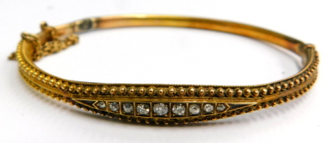 A Victorian hinged bangle, the half hoop design with reeded filigree type decoration, with central diamond set panel, with safety chain on a yellow metal colour band, with later base unmarked, 6cm wide.
