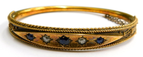 A Victorian 15ct gold hinged bangle, with a diamond shaped top section set, with sapphires and diamonds, with reeded filigree type decoration, with safety chain on hinged support 6cm diameter, 11.7g all in.