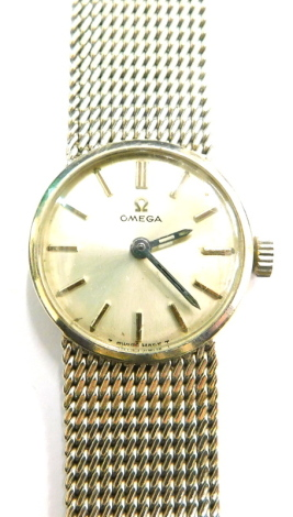 An Omega 9ct white gold ladies wrist watch, with a small circular silvered dial, on bark effect bracelet, 19cm long, with certificate for guarantee dated 1st June 1972, movement number 25749763, 35.5g all in.