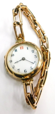 An early 20thC 9ct gold wrist watch, with circular watch head and white enamel dial, with gold markers and blue hands, on a expanding yellow metal bracelet, unmarked, 21g all in.