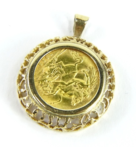 A George V half gold sovereign pendant, dated 1913, in a raised and pierced 9ct gold frame, 6.7g all in.