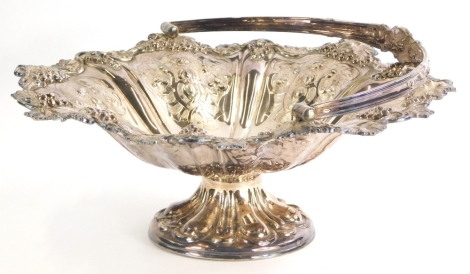 An Edwardian silver plated comport, of shaped form, repousse decorated with berries and scrolls, with swing handle, on a circular foot, 32cm wide, 4½oz.