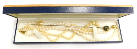 A group of jewellery, comprising a turquoise and paste stone set hat pin, a cultured pearl and 9ct gold clasped pearl necklace 42cm long, and a pearl necklace with a 9ct gold clasp 36cm long. (3)