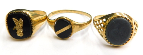 Three 9ct gold signet rings, to include one with pierced design shoulders and warrior lava path central panel, ring size T, a black agate and eagle applied decorated signet ring, ring size S, a further example with black agate and a single yellow metal ap