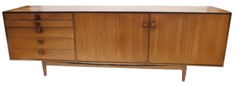 A 1960's teak sideboard, possibly Kefod Larsson for G-plan, with five graduated drawers, and two doors, each with square handles on part turned legs (AF), 77cm high, 235cm wide.