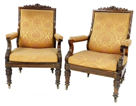 A pair of George IV rosewood library open armchairs, with scrolling cresting rails, padded backs and arms in Damask upholstery and loose seat cushions to match, with scroll arms and turned legs with brass castors. Provenance: Newbold Pacey Hall, Warwicksh