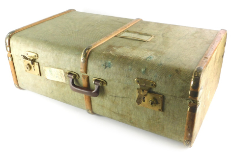 A green canvas and wooden bound suitcase or travel trunk, with brass effect metal mounts, British Railway luggage label for a journey from Cromer Beach to Borehamwood and Elstree, etc., 76cm wide.