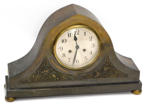 An unusual early 20thC patinated brass mantel clock, of arched form with two panels, each decorated with roses in Arts and Crafts manner, on bun feet, 55cm wide.