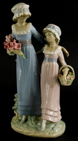 A Lladro porcelain figure group, of a lady with a young girl holding flowers, on oval base, 32cm high.