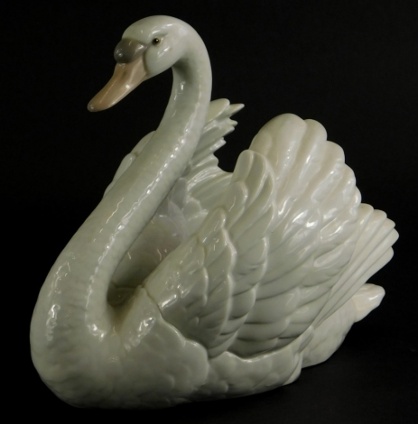 A Lladro porcelain figure of a swan, 20cm long.