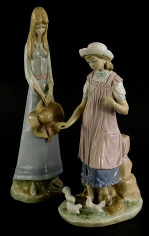 A Lladro porcelain figure of a young girl feeding doves, (AF), 28cm high, and a Spanish porcelain figure of a girl with a broad rimmed hat. (2)