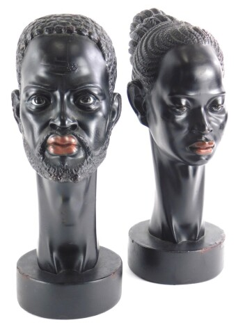 A pair of 1950s/60s ebonised plaster busts, modelled in the form of an African man and lady, each with a long neck on circular base, (AF), 33cm high.