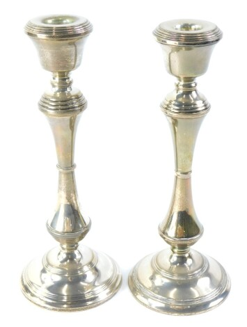 A pair of Elizabeth II silver candlesticks, each with reeded decoration, with a waisted column and domed foot, Birmingham 1974, loaded, 26cm high.