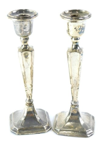A pair of early 20thC silver candlesticks, with a tapering column and canted square base, loaded, marks indistinct, 20.5cm high.
