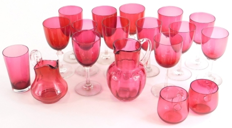 A collection of cranberry tinted wine glasses, a beaker, two small custard cups and two jugs.