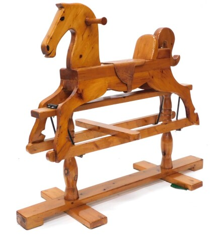 A carved pine child's rocking horse, with leather saddle and ebonised metal mounts, on a trestle base with turned supports, 100cm long.
