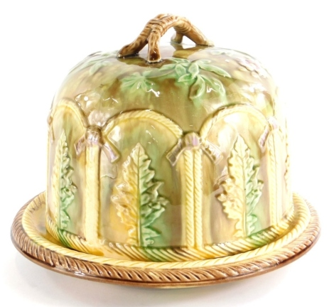 A Victorian majolica cheese dome and cover, decorated with leaves within arched compartments, the base with stylised feather banding and with a stylised twig base, 23cm high.