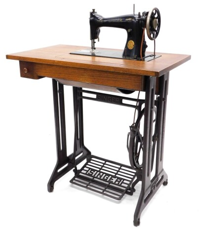 A Singer treadle sewing machine table, the fold-and-reveal machine numbered ED042387, on an oak and cast iron treadle base, 94cm high, 79cm wide.