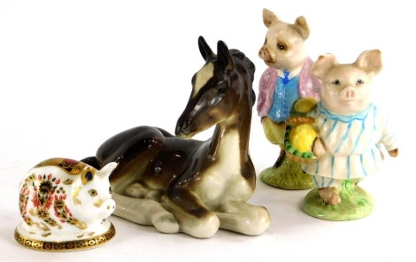 A Beswick ceramic model of Pigling Bland and Little Pig Robinson, brown back stamp, a Royal Crown Derby pig, with silver button, and a Russian model of a recumbent foal. (4)