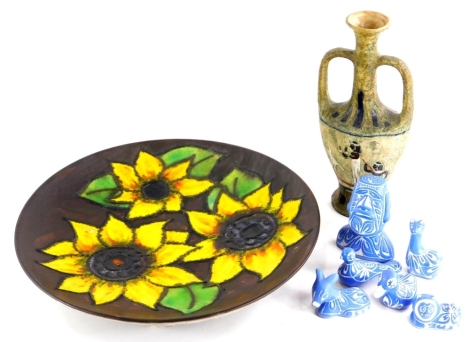 An unusual studio ware plaque, decorated with sunflowers, possibly German, various art pottery figures, with incise decoration and blue glaze, and an Egyptian style two handled vase.