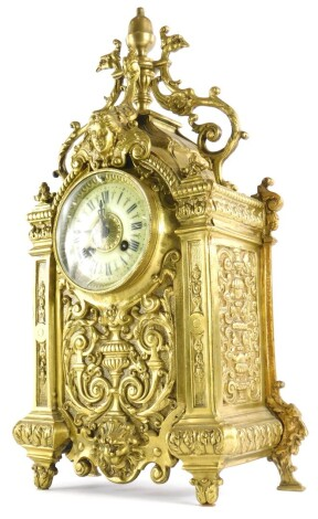 A late 19th/early 20thC French cast brass cased mantel clock, decorated with female mask, rococo scrolls, lion masks, etc., with the enamel style dial with Roman numerals, 48cm high.