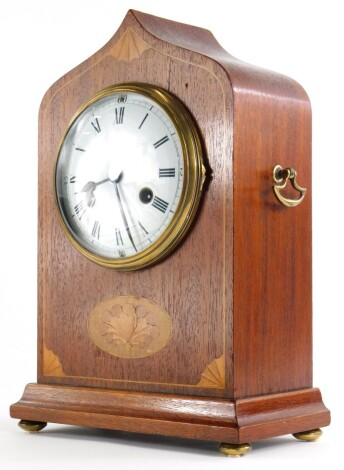 An Edwardian mahogany and marquetry mantel clock, with arched case, the white enamel dial decorated with Roman numerals, flanked by brass handles, on bun feet, 35cm high.