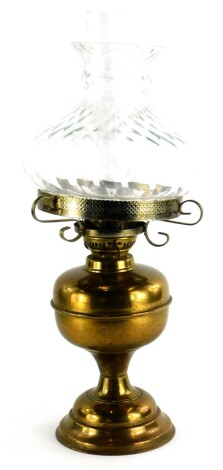 A 20thC brass oil lamp, with clear shade, on domed foot, 52cm high.