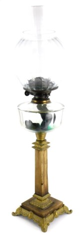 A late 19thC/early 20thC cast brass and alabaster oil lamp, the clear reservoir with faceted decoration on a tapering column, on a square base with scroll cast feet, 49cm high, and a globular glass shade, 18cm high.