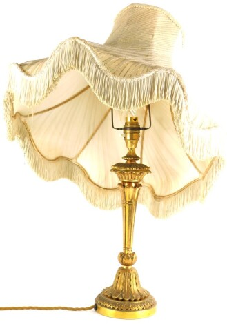 A continental gilt metal table lamp, cast with leaves on a tapering base, with decorative shade with metallic stitching, 57cm high overall.