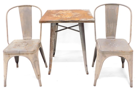 A vintage metal industrial style cafe or garden table, with grey enamel legs, square top and grey enamel painted legs, 73cm high, 60cm wide, and a pair of matching chairs, each with a shaped back and a solid seat, possibly French.