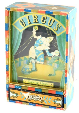 A vintage automaton Circus Dancing Clown articulated musical table ornament, depicting a harlequin in a glazed and paper applied case, with drawer, 21cm high, 14cm wide.