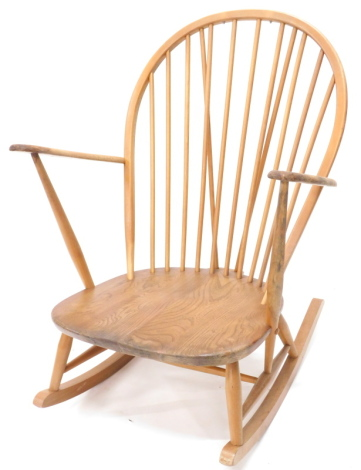 An Ercol rocking chair, the shaped back with spindle turned supports, curved arms and solid elm seat with rockers.