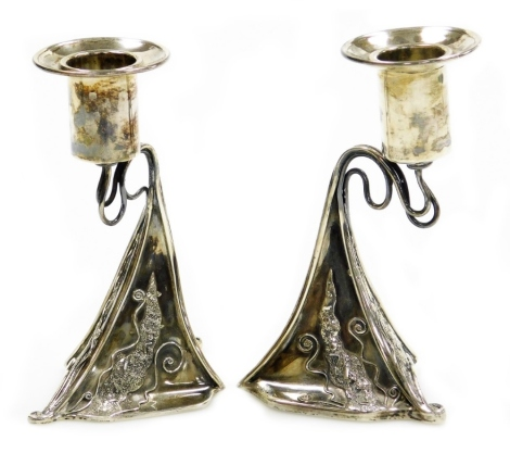 A pair of Arts and Crafts style silver candlesticks, with tapered stem, on shaped body with artistic applied scroll detailing, maker's stamp MJ, Edinburgh, on weighted bases, 13cm high, 12oz gross.