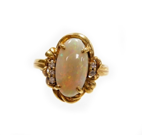 An opal and diamond dress ring, the oval opal in four claw setting with rococo scroll bordering and diamond set shoulders, with three tiny diamonds to one side and two to the other, on a raised shank, yellow metal stamped 750, ring size T, 6.1g all in.