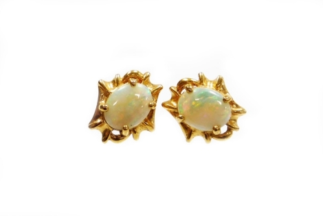 A pair of opal stud earrings, with oval opal in four claw setting, surrounded by abstract twist design bordering, on stem back with butterfly backs, yellow metal unmarked, the back stamped 750, each earring head 1cm high, 5.5g all in.