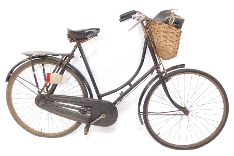 A vintage Raleigh black loop frame bicycle, c1930's, with red trim and Raleigh decal to handlebar upright, cased chain, black leather saddle, S20/1., with metal pannier, front basket and saddle bag, height to saddle 93cm.