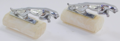 A pair of Jaguar Leaper car mascots, raised on oval cylindrical alabaster bases, 12cm wide.