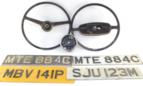 A Smith's vintage dashboard speedometer, with mileometer and fuel gauge, together with two vintage steering wheels, and four number plates. (7)