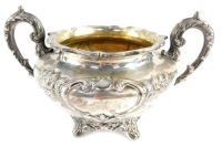 A William IV Scottish silver sugar bowl, of twin handled form, with shield reserves, embossed framed with flowers and rococo scrolls, one presentation engraved 'Presented to John Coutts Esq., Surgeon, Fraserburgh, 20th June 1839', raised on four leaf scro