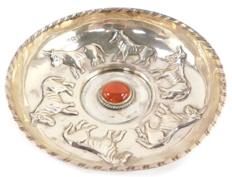 An Edward VII silver dish, embossed with a repeating pattern of six bulls, centred around a red hard stone cabochon, George Nathan and Ridley Hayes, Chester 1907, 5.44oz.