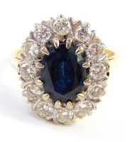 A sapphire and diamond set dress ring, the central oval sapphire in a claw setting, 9.2mm x 6.6mm x 4.8mm, surrounded by twelve round brilliant cut diamonds, each approximately 0.05ct, with pierced shoulders on a yellow metal band, stamped 750, ring size