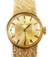 A 9ct gold Tissot lady's wristwatch, with gold coloured small dial, on a bark effect bracelet, the dial 1.5cm wide, 15.5cm long, 20.8g all in.