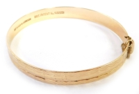 A 9ct gold bangle, with engraved design, of loops and rectangular panels, with safety chain, and slide-over clasp, maker's stamp NYMPH, London, 6cm wide, 13.5g.