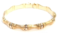 A modern multi-link bracelet, with elongated bark effect finish links, and white gold breakers, with slide end clasp, with safety clip, yellow metal, stamped 375, 19.5cm long, 10.3g.