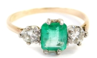 A dress ring, with central rectangular cut emerald in full claw setting, flanked by two round brilliant cut diamonds in claw setting, on a yellow metal band unmarked, possibly 18ct, ring size M½, 2g.